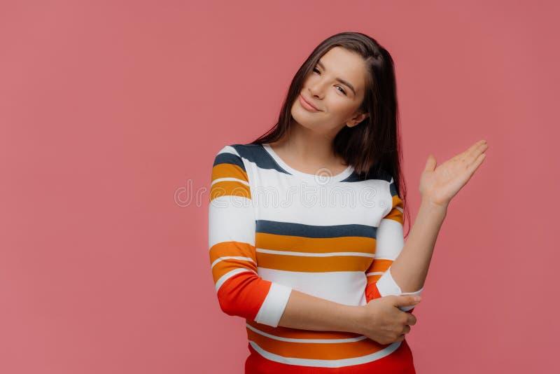 La belle femme démontre quelque chose avec la paume sur l'espace libre, porte le pullover occasionnel rayé, inclinaisons se dirig images stock