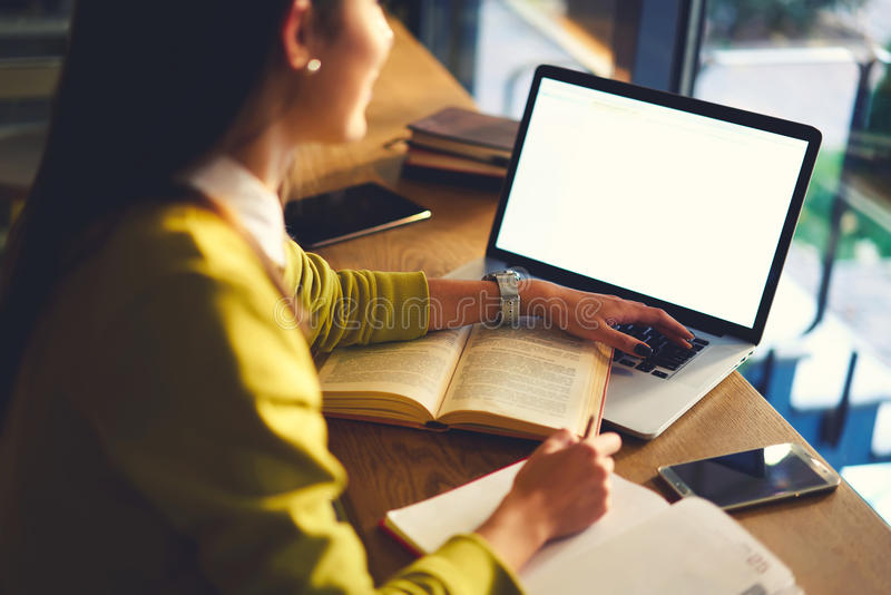 La belle femme d'affaires avec les cheveux foncés et le chandail jaune travaille dans coworking avec l'accès de wifi photos libres de droits