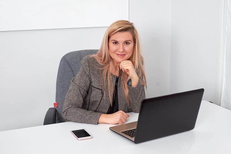 La belle femme d'affaires travaille derrière l'ordinateur portable au bureau photographie stock