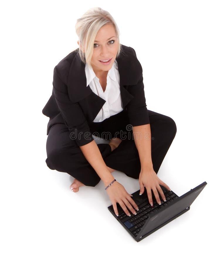 La belle femme d'affaires utilise son netbook photo stock