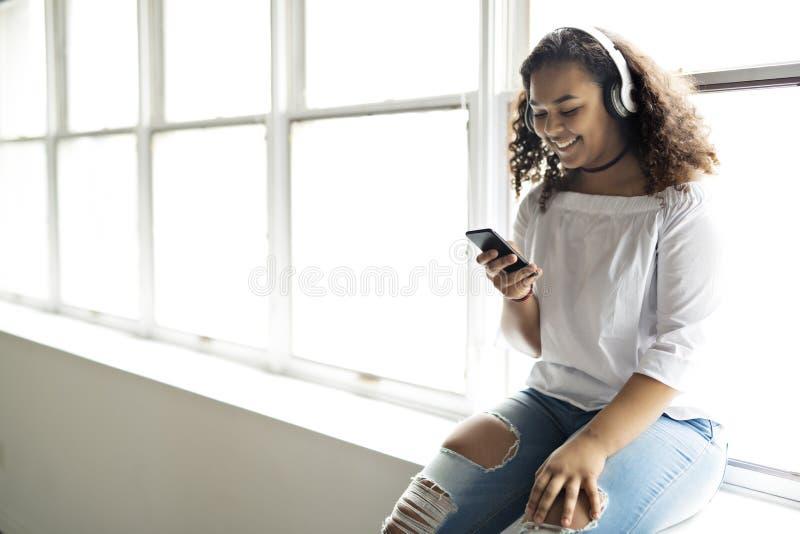 La belle femme d'Afro-américain de jeune adolescent a plaisir à écouter la musique avec des écouteurs photo libre de droits