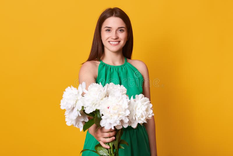 La belle femme d'une chevelure foncée portant le bain de soleil vert avec le bouquet des pivoines blanches fleurit II une main, v images libres de droits