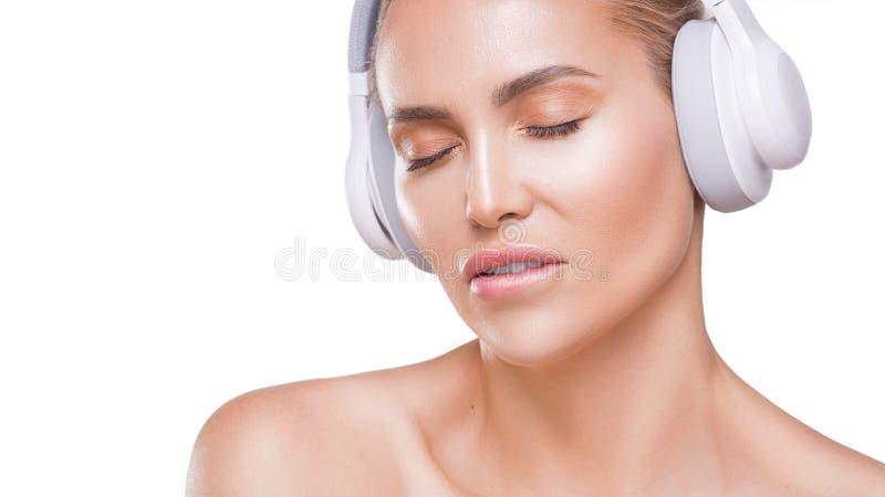La belle femme dans des écouteurs blancs enjoing la musique, a mordu sa lèvre, avec les yeux fermés sur le fond blanc images stock