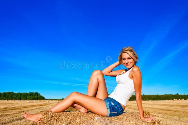La belle femme dans des jeans court-circuitent la pose sur une balle de blé dans un domaine photographie stock