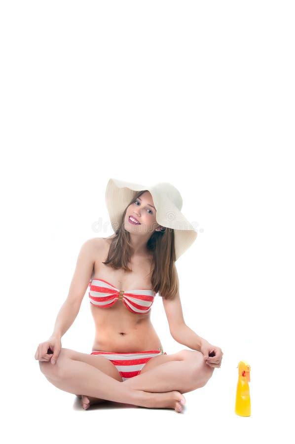 La belle femme dans le bikini s'assied avec la bouteille de jet images libres de droits