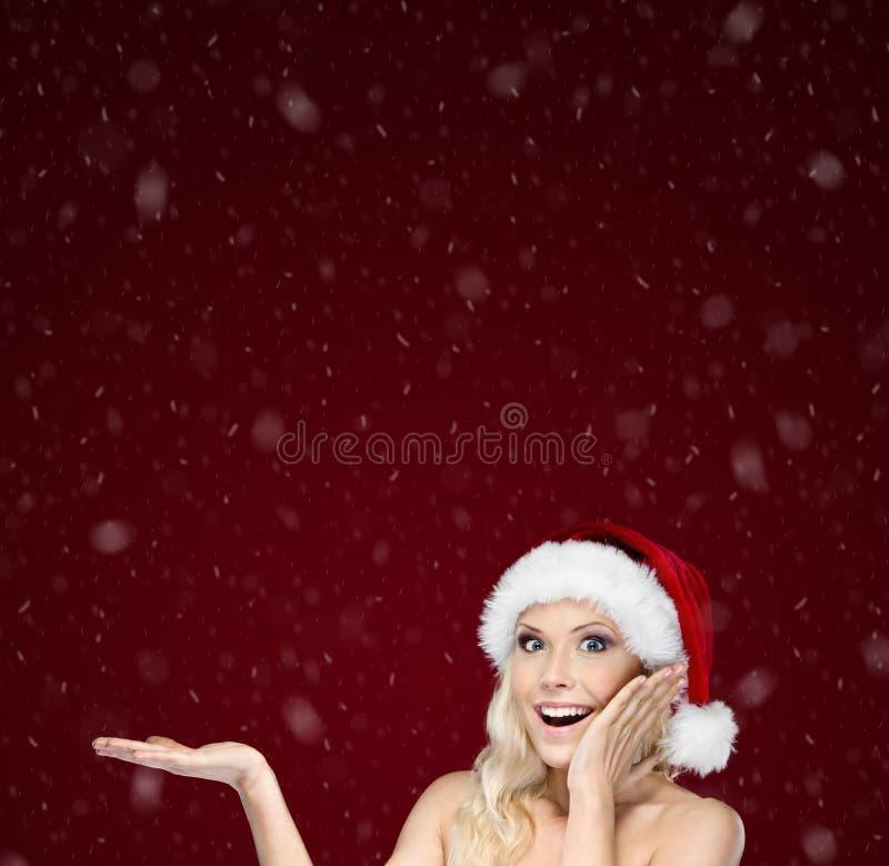 La belle femme dans le capuchon de Noël fait des gestes la paume vers le haut image libre de droits