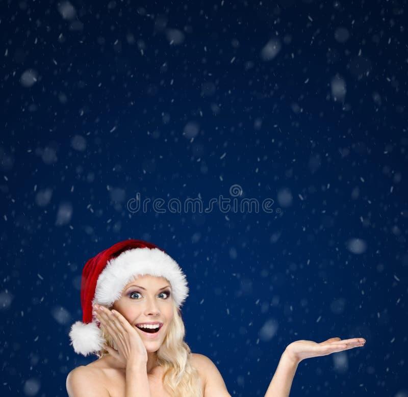 La belle femme dans le capuchon de Noël fait des gestes la paume vers le haut photographie stock libre de droits