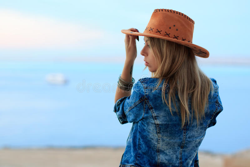 La belle femme dans le style occidental sauvage de cowboy, le chapeau de cowboy et la veste de jeans, photosession de portrait de images libres de droits
