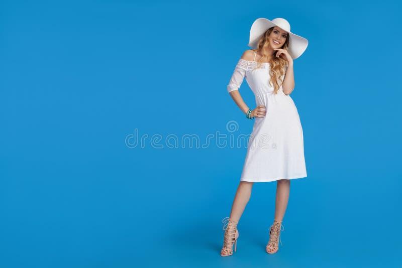La belle femme dans la robe et le chapeau blancs de Sun se tient avec la main sur la hanche et le sourire image stock