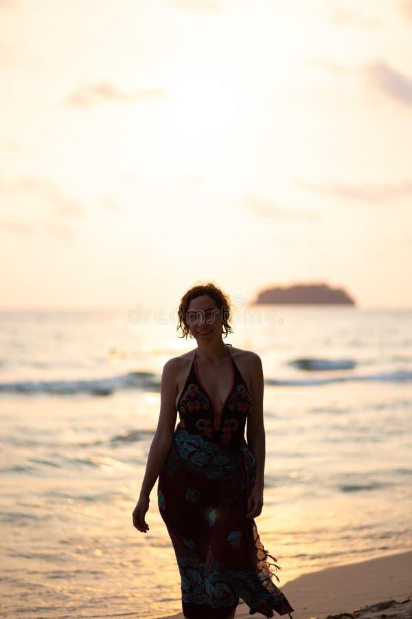 La belle femme dans une robe color?e d'?t? marchant sur la plage de la Tha?lande Ko Chang avec le beau blanc envoient pendant l'a photographie stock