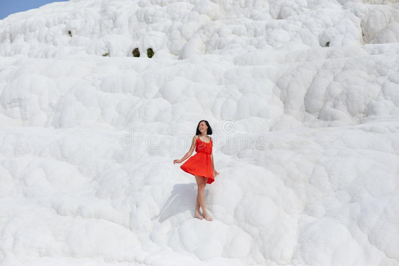 La belle femme dans une robe rouge se tient contre les montagnes blanches Paysage fabuleux, nature stupéfiante Fille sur une roch images stock