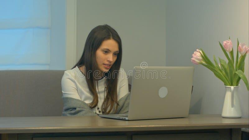 La belle femme de brune habillée dans le blanc parle sérieusement tout en videocalling avec un ordinateur portable image libre de droits