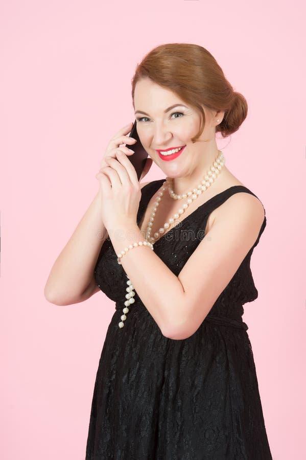 La belle femme de brune parlent au-dessus du téléphone intelligent La femme gaie tient le téléphone Femme dans la robe noire sur  image stock