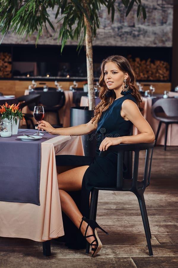 La belle femme de brune s'est habillée dans un verre à vin noir élégant de prises de robe dans un restaurant de luxe images stock