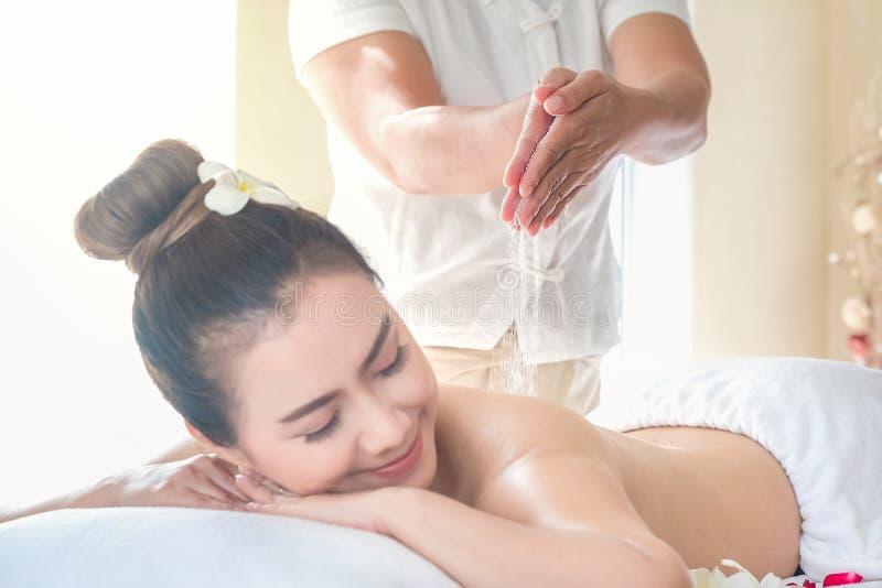 La belle femme de l'Asie appréciant le sel frottent le massage à la station thermale de santé en Thaïlande images stock