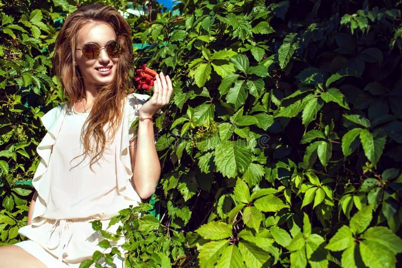 La belle femme de sourire dans le rond à la mode a reflété des lunettes de soleil se reposant sur l'échelle à la haie de plante g photographie stock