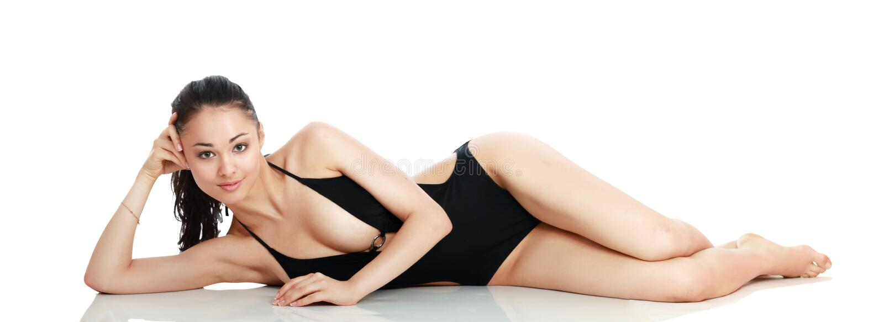 La belle femme de sourire dans un maillot de bain noir est images stock