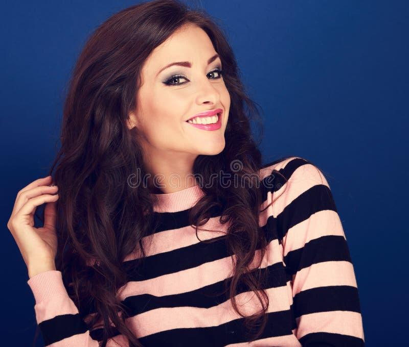 La belle femme de sourire toothy émouvante lui remettent de longs cheveux bouclés image libre de droits