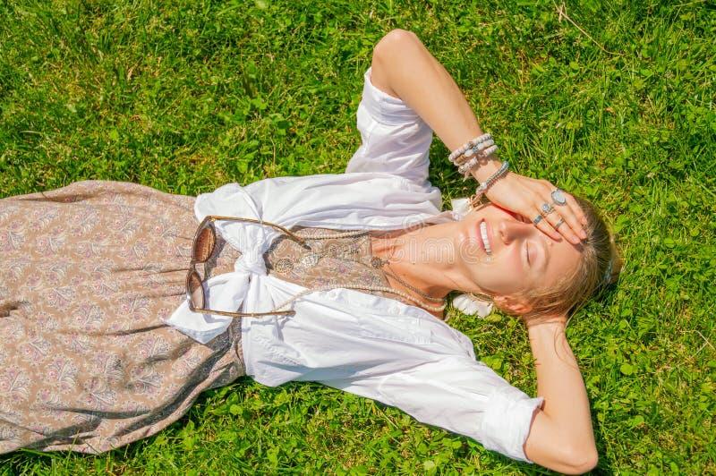 La belle femme de style de boho avec beaucoup d'accessoires se trouve sur l'herbe verte Mometn heureux photo stock