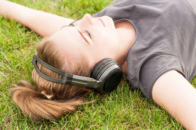 La belle femme en plan rapproché se trouvant sur l'herbe et écoutent musique photos libres de droits