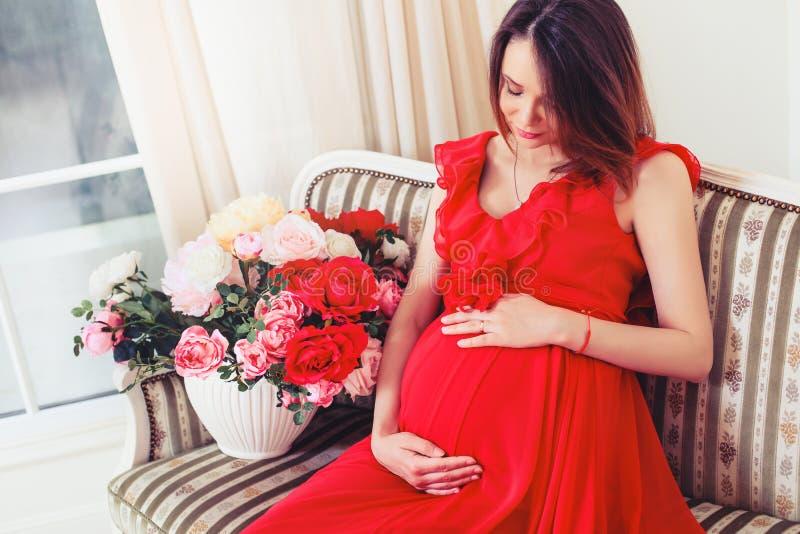 La belle femme enceinte touchant son ventre avec des mains dans le salon ayant, la lumière donnent une atmosphère confortable images libres de droits