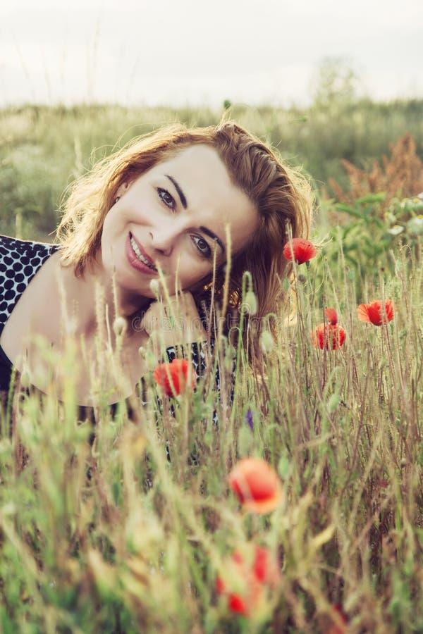 La belle femme est souriante et posante dans le domaine de fleurs de pavot images stock