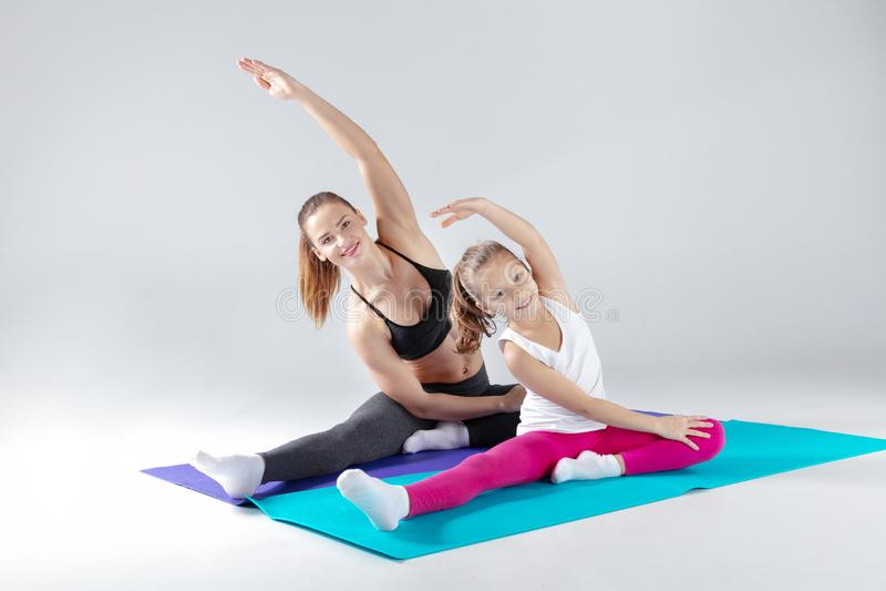 La belle femme et sa petite fille font des exercices sur des tapis image libre de droits
