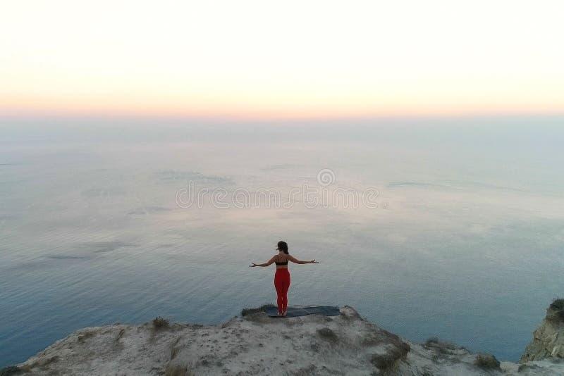 La belle femme fait stretcing et méditation de yoga sur le dessus de la montagne avec la vue de mer au coucher du soleil Silhouet photographie stock libre de droits
