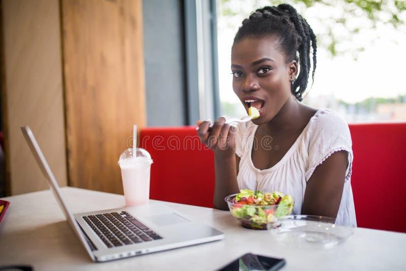 La belle femme font manger le lanch de la salade au dîner se reposant au café Jeune femme d'afro-américain s'asseyant dans un caf photo libre de droits