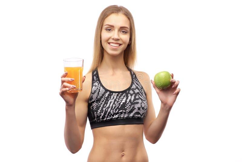 La belle femme habillée dans les sports supérieurs, juge le jus d'orange et l'Apple vert, regardant directement dans la caméra photos libres de droits