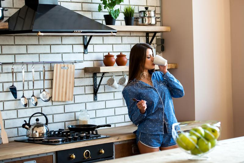 La belle femme heureuse de brune est dans la cuisine avec une tasse de thé ou de café dans des pyjamas bleus La hausse de début d photos libres de droits