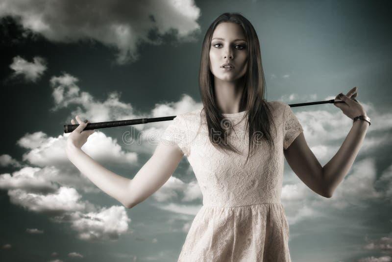 La belle femme joue au golf avec le golf-club image libre de droits