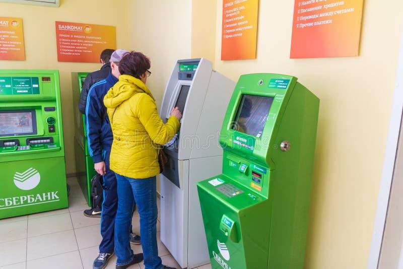 La belle femme mûre paye des utilités par une atmosphère Texte dans le Russe : Sberbank, atmosphère image libre de droits