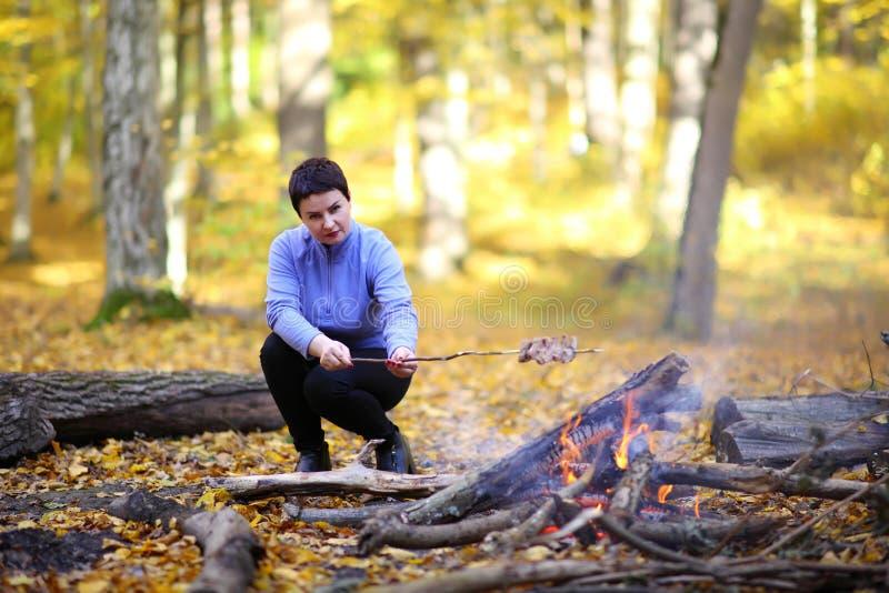 La belle femme mûre sur un pique-nique dans la femme de la forêt A fait cuire le lard sur un feu, ficelé sur un bâton image libre de droits
