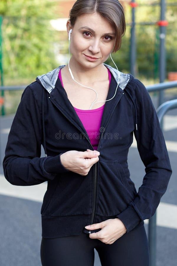 La belle femme mince âgée moyenne ferme la fermeture éclair des vêtements de sport, souriant, sur le sportsground extérieur Écout image libre de droits