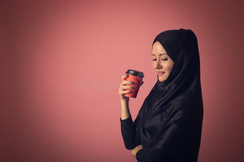 La belle femme musulmane avec un regard mystérieux boit du café d'une tasse rouge sur un fond rose dans le studio images stock