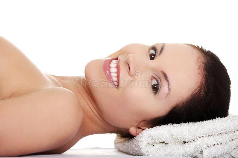 La belle femme nue se trouve et sourit. photographie stock