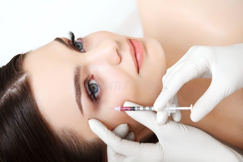 La belle femme obtient l'injection dans son visage. Chirurgie esthétique photos stock