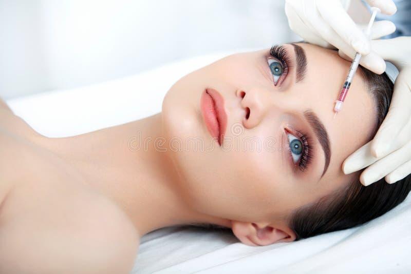 La belle femme obtient l'injection dans son visage. Chirurgie esthétique photo libre de droits
