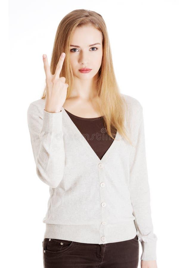 La belle femme occasionnelle montre le signe de victoire, deux doigts. image libre de droits