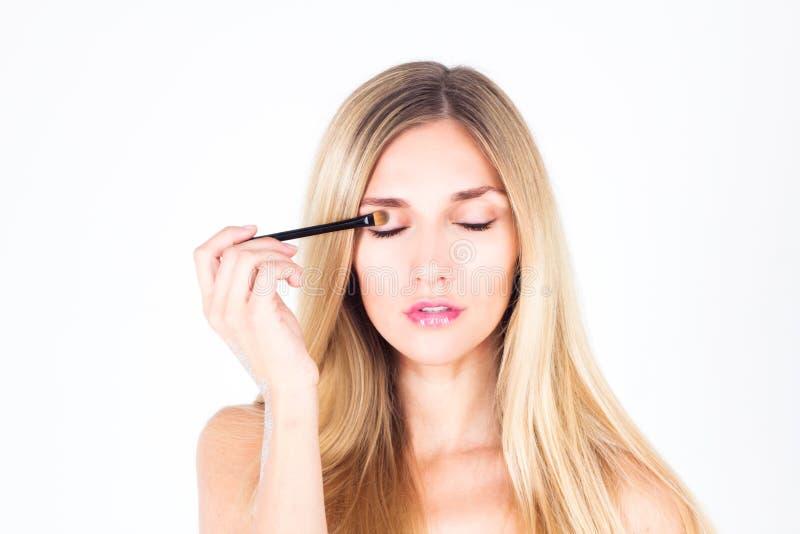 La belle femme peint la paupière avec une brosse cosmétique la femme avec le bâton photos stock