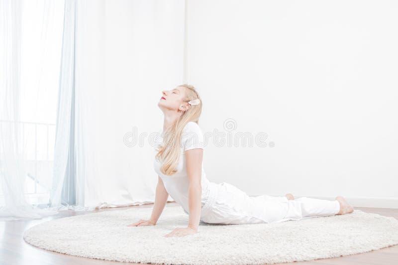 La belle femme pratique le yoga à la maison, faisant l'exercice de cobra, pose de Bhujangasana photos stock