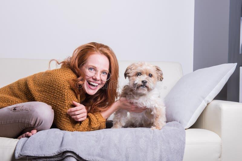 La belle femme rousse instruit son chien sur le divan images libres de droits