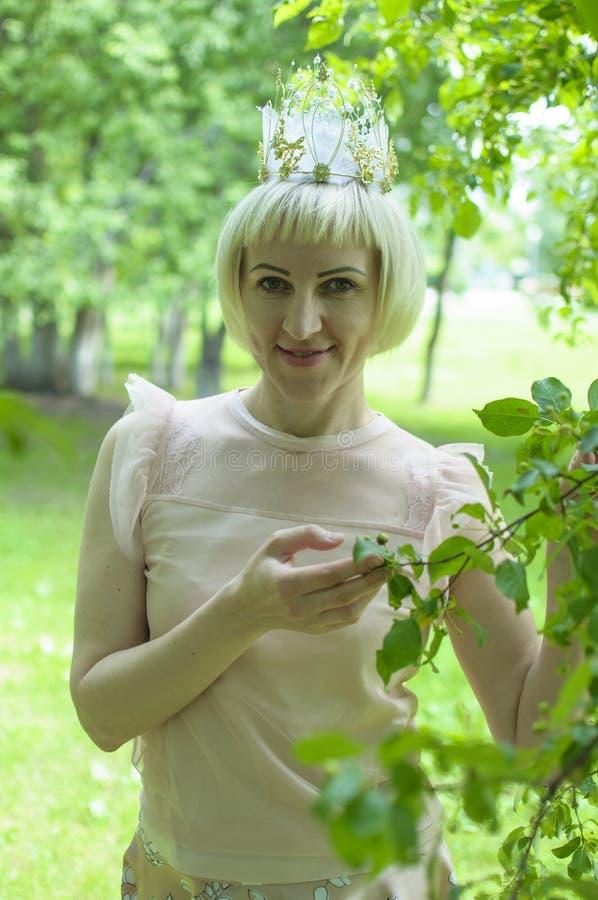 La belle femme russe avec une couronne sur les promenades principales dans la forêt pendant l'été photographie stock libre de droits