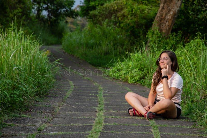 La belle femme s'asseyant sur le chemin célèbre de tuiles a entouré par nature dans Bali et x28 ; L'Indonésie photos stock