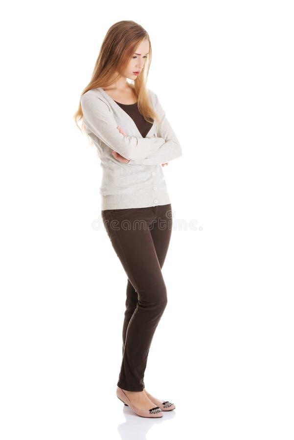 La belle femme se tient, des lookis tristes, avec ses mains croisées. photo stock