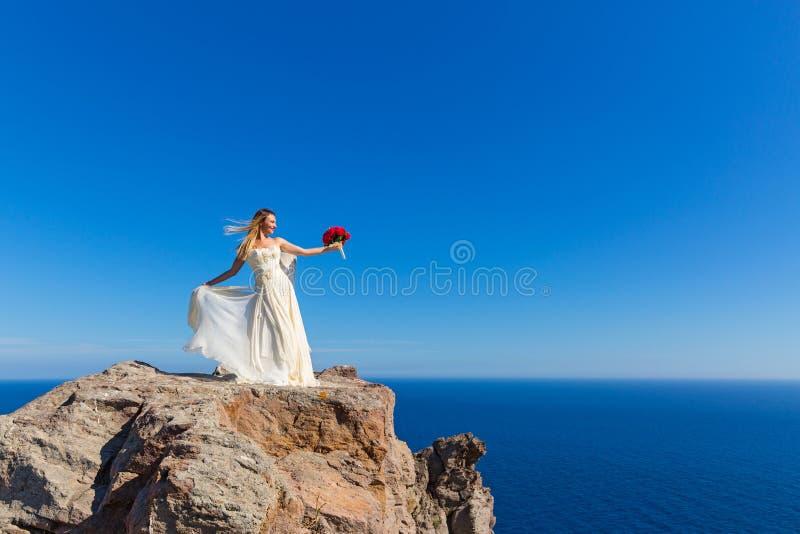 La belle femme se tient sur une haute falaise photo stock