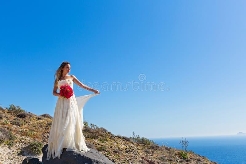 La belle femme se tient sur une haute pierre photographie stock libre de droits
