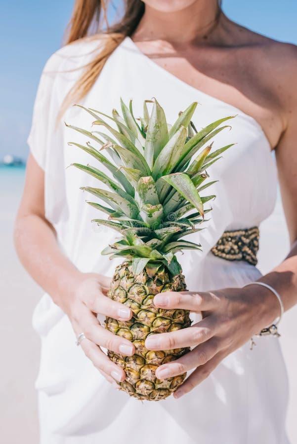 La belle femme se tient sur une plage sablonneuse blanche à côté de l'océan Une fille dans une robe blanche tient un ananas jaune photo stock