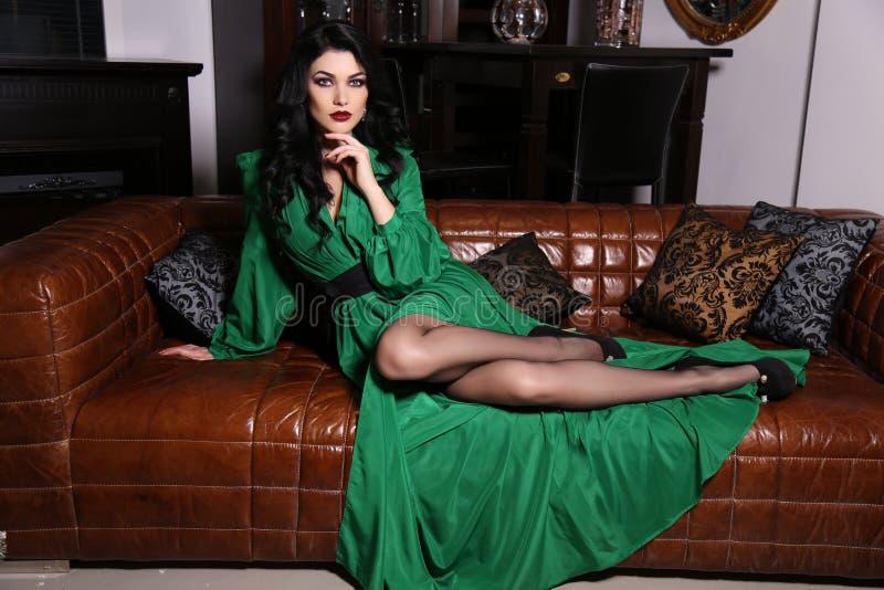 La belle femme sensuelle avec les cheveux foncés porte la robe verte élégante, photographie stock